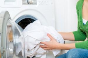 Frau legt Wäsche in Trockner